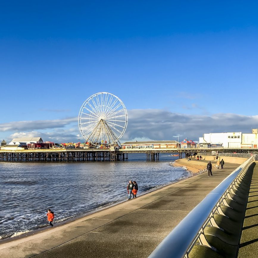Panoramic view along the promenade at Blackpool, UK.  Blackpool tower can be seen in the distance and Blackpool pier can be seen on the left of the phtograph.  People can be seen walking on the promenade.